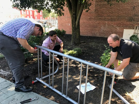 Volunteers with Bicycle Friendly Shippensburg initiative install the first of a series of bicycle racks, at the University Grille in downtown Shippensburg.