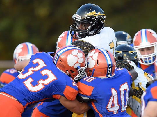 D'Iberville's Jaden Walley (7) is gang tackled by the