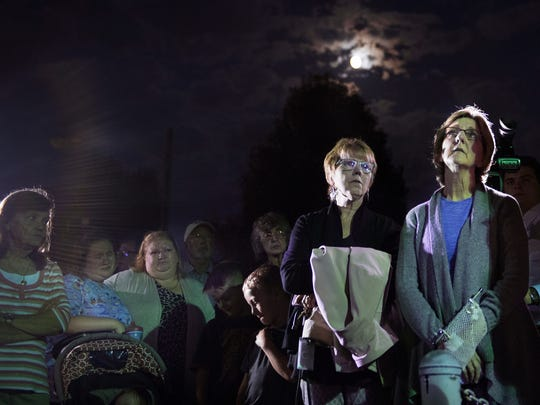 Rosemary Hehns, of Springville, Tenn., and Jennifer Wright, of Paris, Tenn., stand in silence Monday, October 2, 2017, during a prayer service in memory of Las Vegas shooting victim Sonny Melton in Big Sandy.
