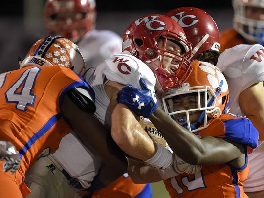 Warren Central's Walt Hopson (center) is tackled by Madison Central's Kenneth Ndebele (left) and Jon Malone on Friday, October 6, 2017, at Madison Central High School in Madison, Miss.