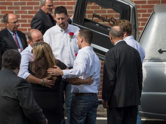 Heather Melton is comforted Tuesday, October 10, 2017, after Sonny Melton's funeral at Big Sandy High School.