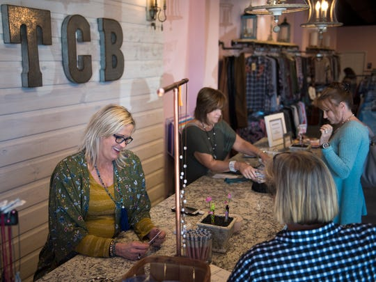 Rhonda Moubray, of Milan, laughs with customer and friend Jane Kroeger, of Jackson, as  Theresa Jenkins, of Trenton, serves customers Wednesday, Oct. 25, 2017, at The Corner Boutique's new location in Jackson.