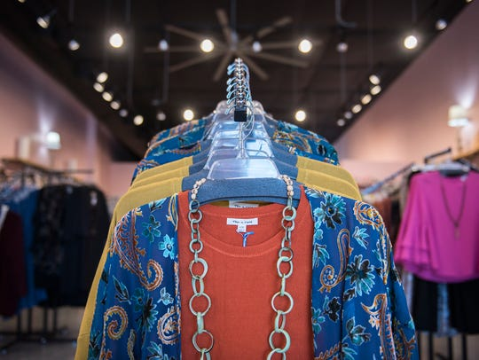 A cardigan with velvet details is displayed among racks