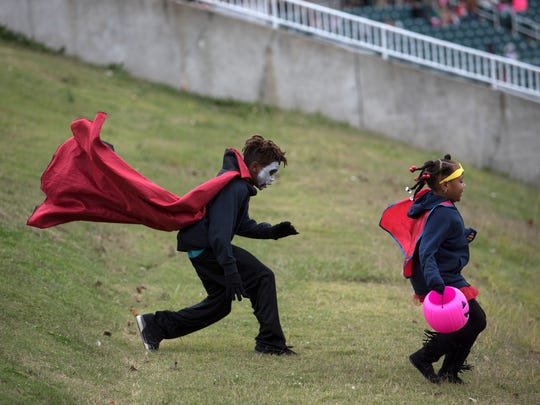 Costumed children run down a hill Saturday, Oct. 28, 2017, during the 10th annual Jackson-Madison County Trunk or Treat at the Ballpark at Jackson.