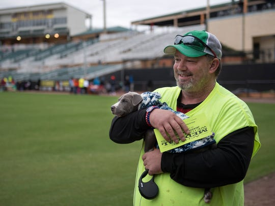 Jeff Hill, of Jackson, carries 2-month-old puppy D-Bow