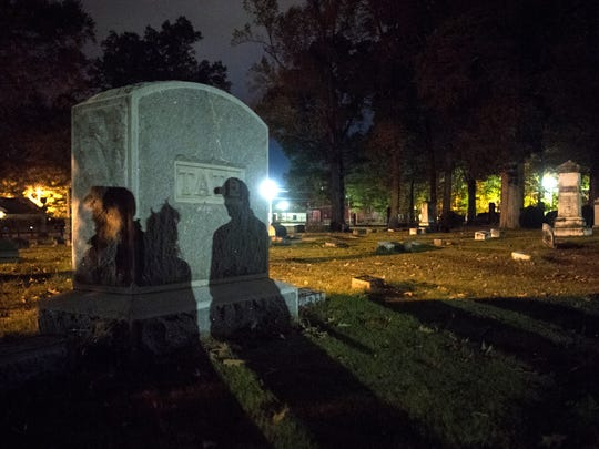 """Ghost tour attendees cast shadows on gravestones as they are guided through Polk Cemetery on Saturday, Oct. 28, 2017, during Epic Haunted Tours' """"History, Legends & Maybe Some Ghosts Tour"""" in Bolivar."""