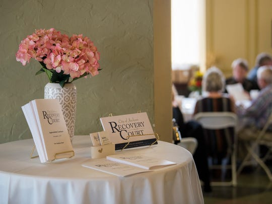 Flowers, programs and card adorn a table Wednesday, Nov. 1, 2017, during the City of Jackson Recovery Court's Appreciation Luncheon at the New Southern Hotel in Jackson.