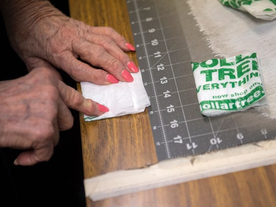 June Ksiezak, of Jackson, measures folded strips of plastic bags Tuesday, Nov. 7, 2017, after cutting them in her workspace at Concordia Lutheran Church in Jackson. One sleeping mat takes 35 hours to make, Ksiezak said.