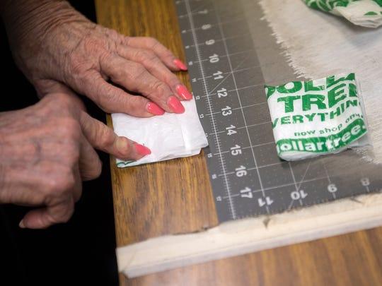 June Ksiezak, of Jackson, measures folded strips of