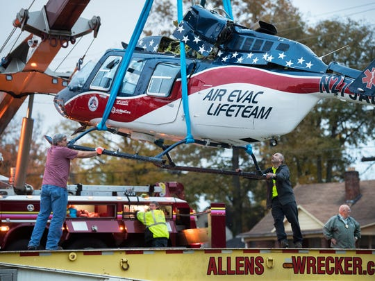 Allen's Towing and Recovery employees help guide a medical chopper onto a trailer Wednesday, Nov. 8, 2017, after it crash landed in the area of Harrison Street and South Home Street in Union City.