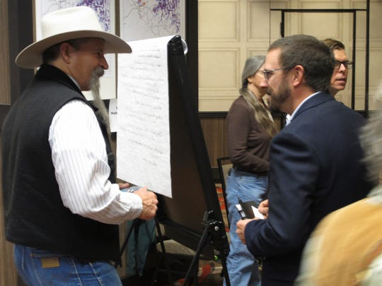 John Ruhs, left, acting deputy director of the U.S. Bureau of Land Management, talks to Patrick Donnelly, Nevada state director for the Center for Biological Diversity, during a public meeting on federal management of the greater sage grouse in 11 western states on Wednesday, Nov. 7, 2017  in Sparks, Nev.  Federal scientists and land managers who've been crafting strategies to protect sage grouse habitat across the West for nearly two decades are going back to the drawing board under a new Trump administration edict to reassess existing plans condemned by ranchers, miners and energy developers.  (AP Photo/Scott Sonner).