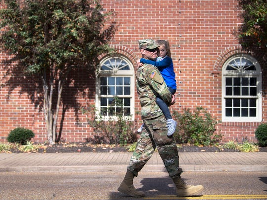 Sgt. Matthew Brown, of Jackson, carries his 5-year-old