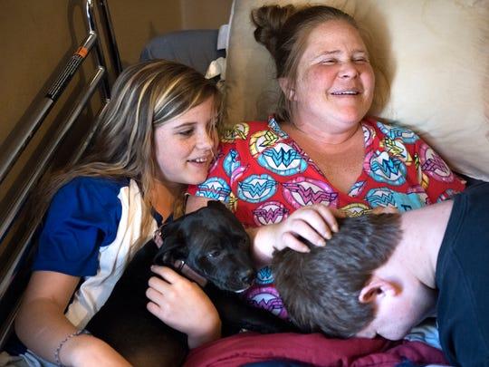 Natosha Holder and her 12-year-old daughter, Sarah Holder, chuckle as Natosha's 14-year-old son, Dawson Holder, drops his head in her lap Friday, Nov. 10, 2107, in the family's Beech Bluff home.