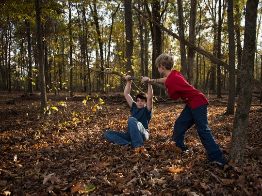 Nick Zeto, 14, of Jackson, and 9-year-old Seth Parkerson, of Jackson, struggle to bring down a tree Friday, Nov. 17, 2017, during HomeLife Academy's North Park Wilderness Adventure in Jackson. The pair was looking for firewood in the woods behind the group's campsite, but were unsuccessful in breaking the tree.