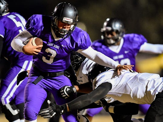 Cane Ridge's Kory Andrews (3) takes a hit from Whitehaven's Marquis Traylor (4) during the first half of the Class 6A semifinal at Cane Ridge High School in Antioch, Tenn., Friday, Nov. 24, 2017.