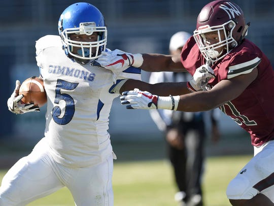 Simmons' Marquez Pam (5) stiff arms Nanih Waiya's Christopher Smith (21) on Friday in the 1A state championship game in Oxford.
