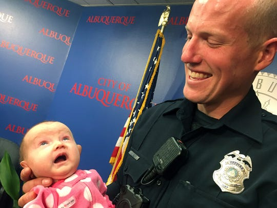 Albuquerque officer Ryan Holets holds his newly adopted daughter, Hope, after being recognized by the city of Albuquerque on Monday, Dec. 11, 2017. In September, Holets convinced a pregnant woman he found using heroin to let him adopt her unborn child. That baby, Hope, is now recovering for being born with an addiction. Holets and his wife have four other children.