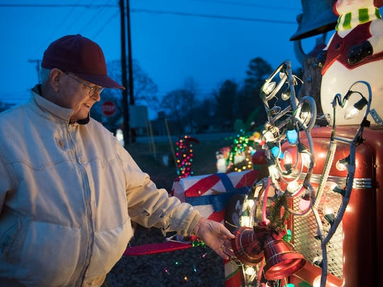 Staley Holder, of Pinson, smiles as he touches the new bells around the neck of a snowman Tuesday, Dec. 5, 2017, at the corner of Circle Drive and US-45 in Pinson. Holder built the snowman from rebar about 35 years ago and the piece has remained one of his favorites ever since.