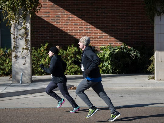 Brittany Stenberg, of Mackenzie, and Kory Pearson, of Jackson, sprint toward the finish line Monday, Jan. 1, 2018, during LIFT Wellness Center's fourth annual Commitment Day 5K race in Jackson. All proceeds benefited Regional Inter-Faith Association of Jackson.