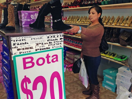 Martha Isabel Velasquez looks at a pair of boots while shopping in downtown Nogales, Ariz. Velasquez says she waited two hours in line to cross by foot over from Nogales, Sonora, Mexico, to go shopping. (AP Photo/Astrid Galvan)