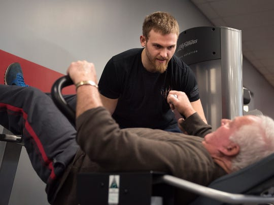 Trainer Chad Blackwell encourages his client, Jack Hornsby, in his final set of 50 crunches on Friday, Jan. 5., 2018, during his personal training session at Maximum Health & Fitness in Jackson.