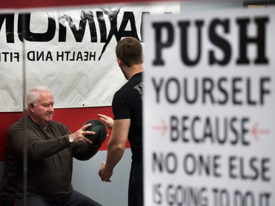 While wall sitting, Jack Hornsby, of Jackson, completes exercises with a medicine ball under the supervision of trainer Chad Blackwell on Friday, Jan. 5., 2018, during his personal training session at Maximum Health & Fitness in Jackson.