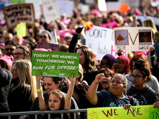 Marchers hold signs during the Women's March in Nashville,