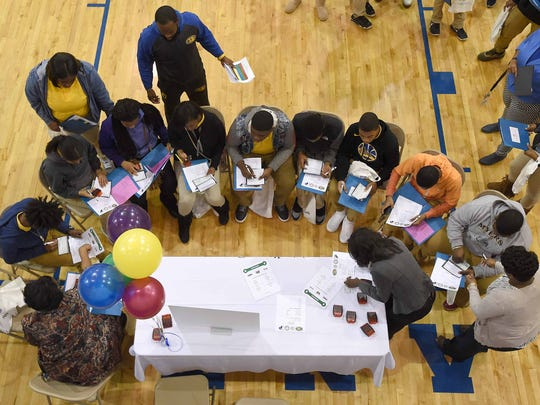 Students pull out their checkbooks at one of the 14 stations at the Reality Fair for 208 ninth graders in the Canton High School gym. The Fair was hosted by the Madison County Business League & Foundation and the Canton Public Schools District.