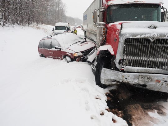 Vehicles rest along the snowbound shoulder along Interstate