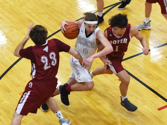 Coshocton's Gaven Williams splits a pair of Dover defenders.