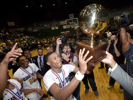 Olive Branch's D.J. Jeffries receives with the Class 5A trophy in the finals of the MHSAA C Spire State Basketball Tournament at the Mississippi Coliseum in Jackson, Miss., on Friday, March 9, 2018.
