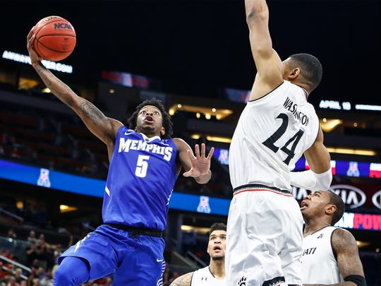 Memphis guard Kareem Brewton Jr. (left) drives for a layup against Cincinnati defender Kyle Washington (right) during second action of their AAC semifinal tournament game in Orlando, Fl., Friday, March 10, 2018.