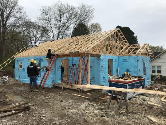 Volunteers from United Structural Systems work to build a Habitat for Humanity home in Ashland City on Sunday, April 8.