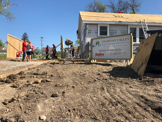 Volunteers construct a garage next to a home Hy-Vee