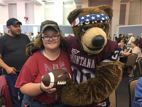 Montana fan Candace Faller gets her football signed by Monte last year year's Grizzly Coaches' Barbecue at the Mansfield Convention Center in downtown Great Falls.