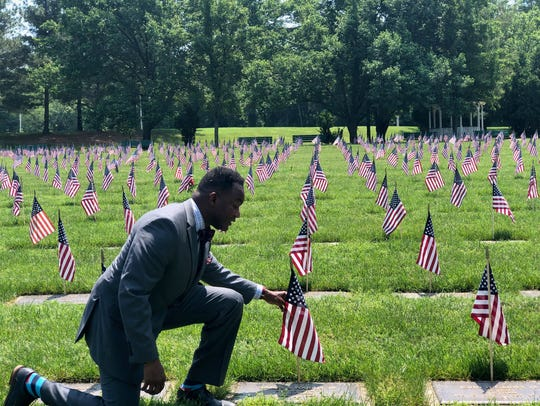 Larence Kirby, the executive director of Delaware Commission of Veterans Affairs, kneels down by a flag to pay respects Saturday at the Delaware Veterans Memorial Cemetery.