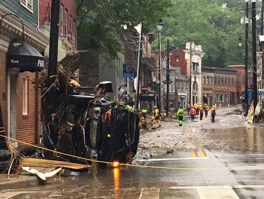 Rescue personnel walk along Ellicott City's Main Street