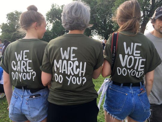 """Ann Delevante,  center, and her daughters show off their shirts during the Families Belong Together rally in Nashville.""""As a mom, this issue is a no brainer,"""" said Delevante, """"They're not refugees, they're people."""""""