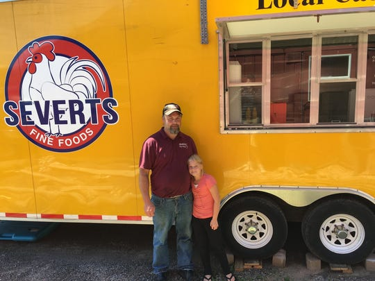 Owner of Sever'ts Fine Foods  Mike Fitzgerald, left, poses for a picture next to his food truck with his daughter Ashley.