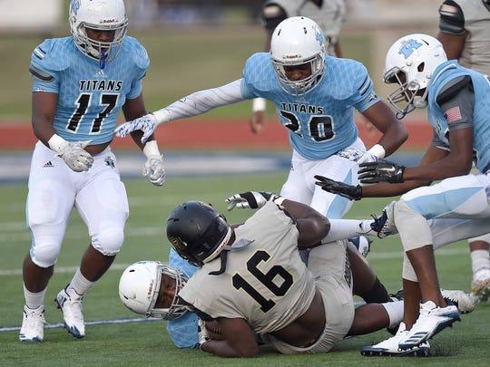 The Titans defense swarms to Northwest Rankin ball carrier Cameron Carroll (16) on Friday, August 25, 2017, at Ridgeland High School in Ridgeland, Miss.