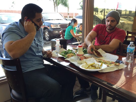 Nas Juma, 22, left, and Omar Ghanim, 23, enjoy Lebanese pizza at Forn Al Hara restaurant in Orange County's Little Arabia in Anaheim, Calif., Tuesday, March 22, 2016.