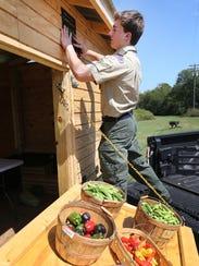 Boy Scout Casey Couch places a plaque on a veggie cart,