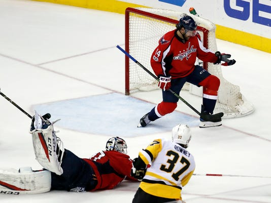 Washington Capitals right wing Justin Williams (14) blocks a shot by Pittsburgh Penguins right wing Carter Rowney (37) with Capitals goalie Braden Holtby (70) out of the net, during the third period of Game 7 in an NHL hockey Stanley Cup Eastern Conference semifinal, Wednesday, May 10, 2017, in Washington. The Penguins won 2-0. (AP Photo/Alex Brandon)