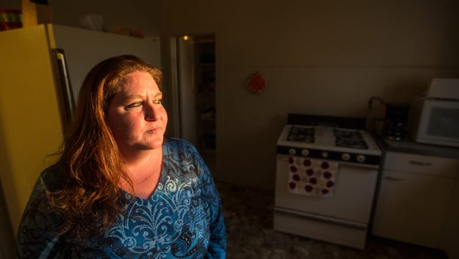 Heather Costello stands in the kitchen at the apartment she moved into last week in Sioux City. The mother of two has been working for a year but living in a homeless shelter.
