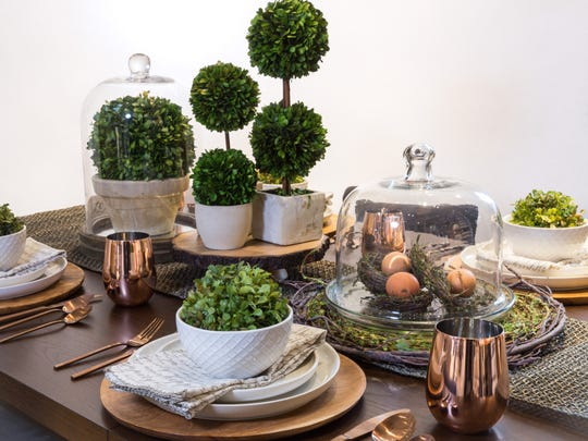 Incorporating rustic materials, such as textured wood, and glass serving trays with boxwood plants create a mix of rustic with a transitional edge.