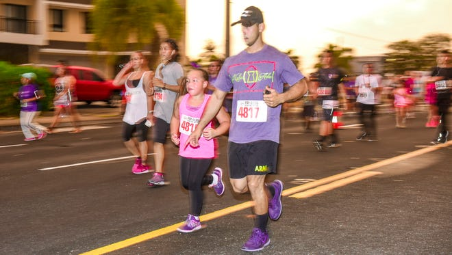 Participants of all ages enjoy the safety of closed-off lanes of traffic on Marine Corps Drive during the 22nd annual Pay-Less Kick the Fat 5K Run/Walk in Hagåtña on March 24, 2018.