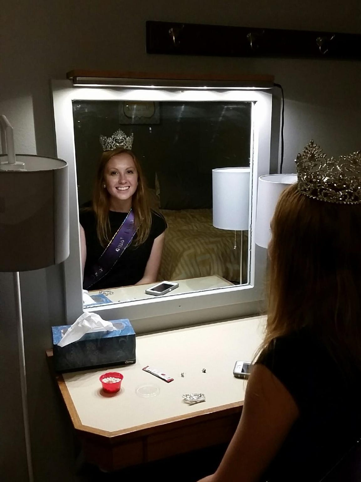 "Elizabeth ""Izzy"" Glover, the reigning Iowa State Fair Queen crowned in 2014, smiles in the mirror inside her fair dorm room."