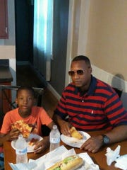 Isaiah Jamison (left) enjoys some pizza and turkey subs with his dad Tyrone Williams.