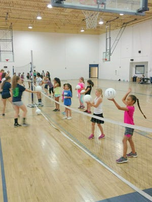 Campers practice hitting the ball over the net during the Silver High volleyball youth camp that will end Thursday.