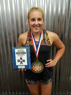 Galion senior Kylie Redman poses with her medal and plaque after setting the national high school record in the bench press